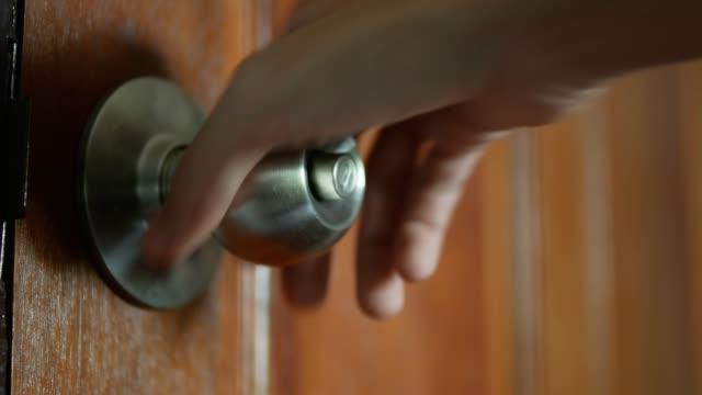 Hand holds door knob and pulls to open the door.