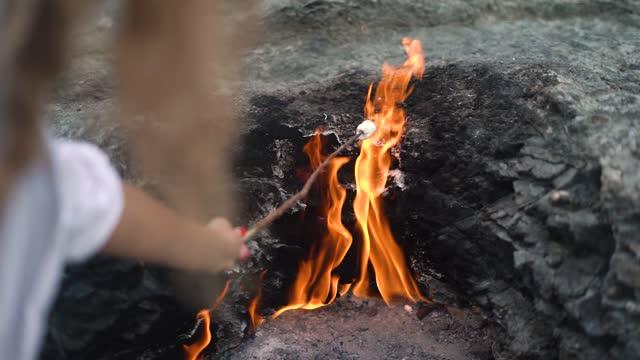 Hand holds marshmallow over blazing Chimaera mountain fire