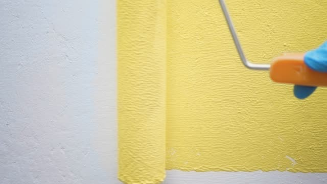 Hand in blue glove slowly paints white wall with roller from right to left and back in yellow. Slow motion and close up view