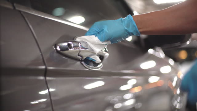 vídeos de stock e filmes b-roll de hand in glove wiping down door handle surfaces of gray car cleaning covid-19 virus in parking lot of supermarkets - limpo