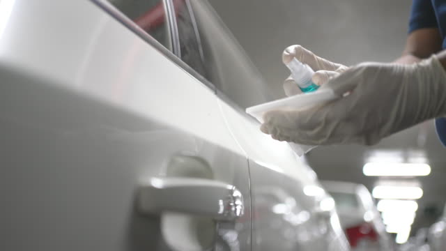 Hand in Glove wiping down door handle surfaces of white car  cleaning covid-19 virus in parking lot of apartment