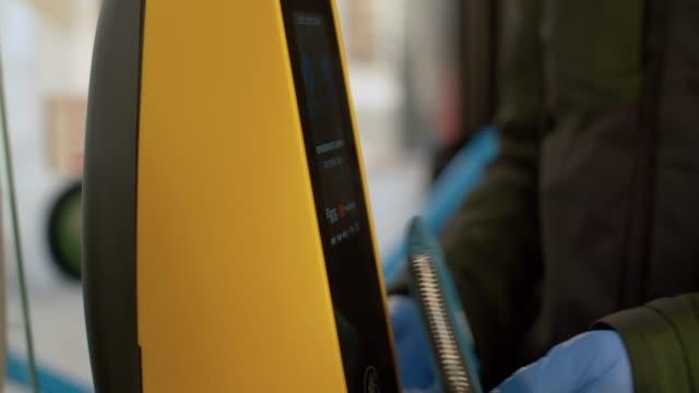 mano in guanti protettivi che pagano in autobus - fare video stock e b–roll