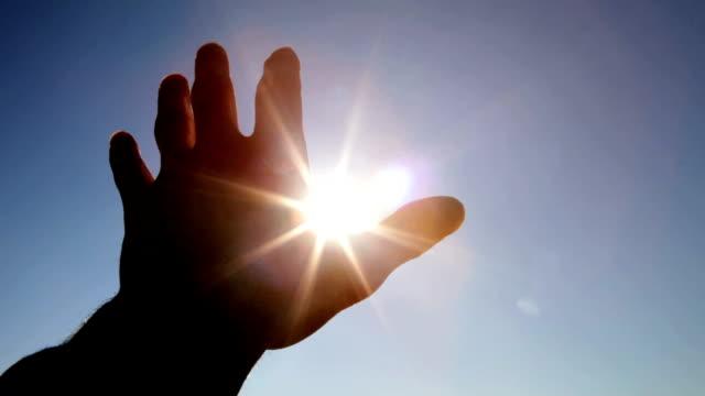 vídeos de stock e filmes b-roll de mão em silhueta contra o sol - retroiluminado