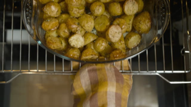 vídeos de stock e filmes b-roll de hand in stove mitten get out golden potato from the oven, top view - assado no forno