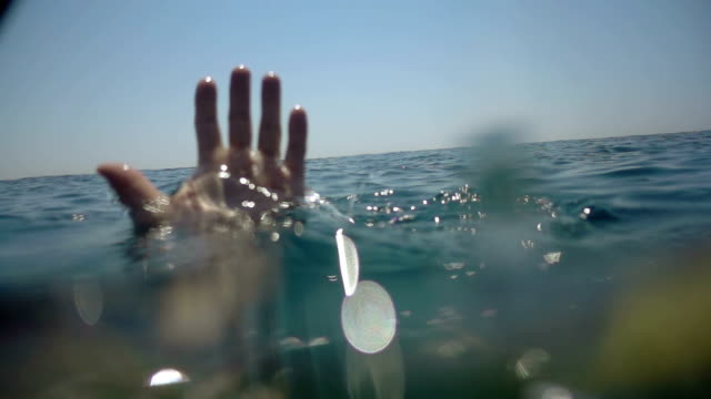 a hand in the water calling for help. - parola video stock e b–roll