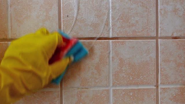 рука в желтой защитной перчатке моет плитку пеной на фоне керамической плитки. - мозаика стоковые видео и кадры b-roll