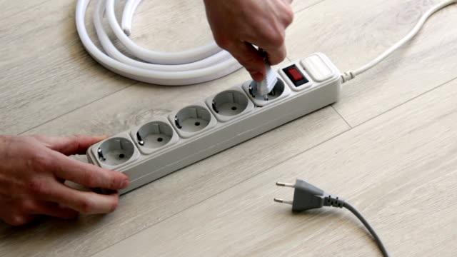 vidéos et rushes de la main insère les bouchons dans le cordon d'extension. - vidéos de rallonge électrique