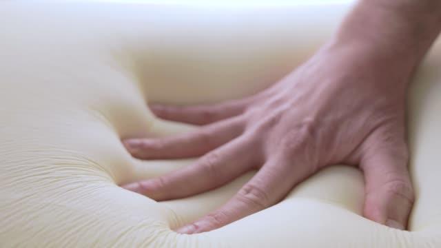 la mano sta toccando un letto di schiuma di memoria - gommapiuma video stock e b–roll