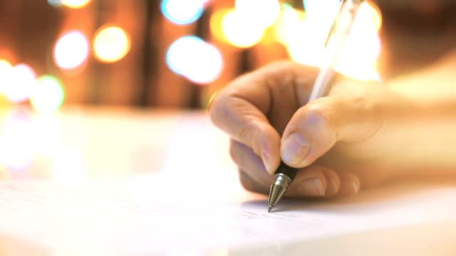 vídeos de stock, filmes e b-roll de mão está escrevendo a carta. luzes de natal em fundo - correio correspondência