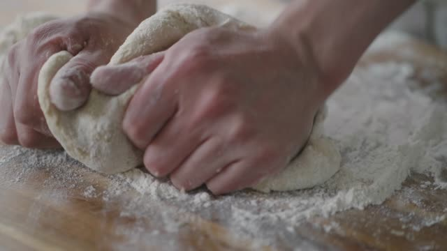 hand knead scone dough on wooden board