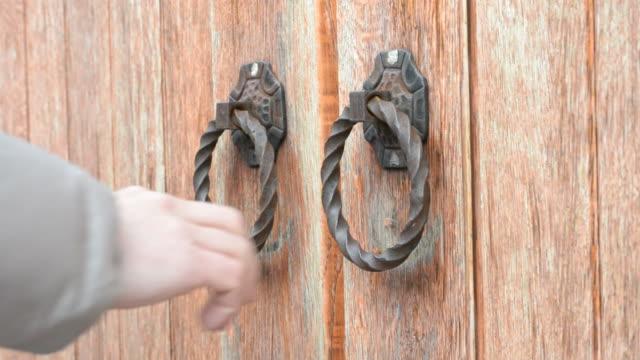 vídeos de stock e filmes b-roll de mão batem no antiquado antiga porta ou portão de madeira - door knock