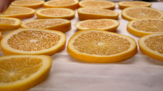Hand lay orange slices on baking paper. Close up.