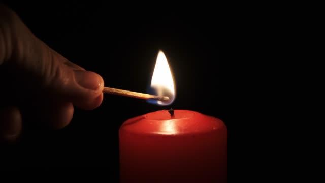 vídeos y material grabado en eventos de stock de luz de mano vela roja con un fósforo, fondo negro. - hanukkah