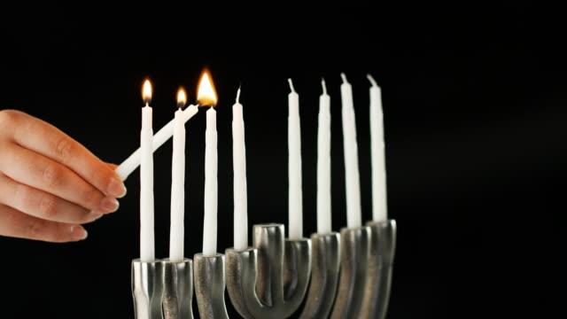vídeos y material grabado en eventos de stock de iluminación de la mano las nueve velas blancas en una menorah judía se sentaban en un pálido mármol superficie, vista lateral, primer plano detalle - hanukkah