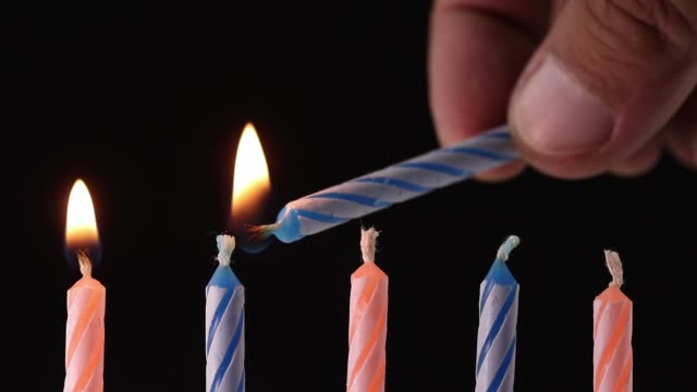 hand lighting up birthday candles on black background - cinque oggetti video stock e b–roll