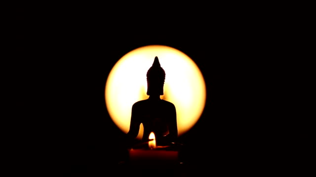 hand lighting up incense stick in front of  Buddha statue video