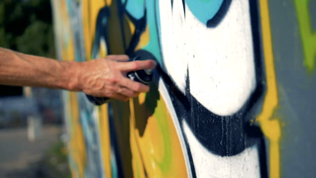 A hand makes black lines with graffiti paint.