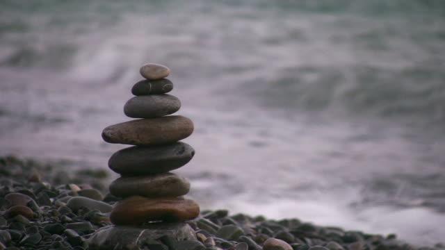 hand making pyramid on beach video