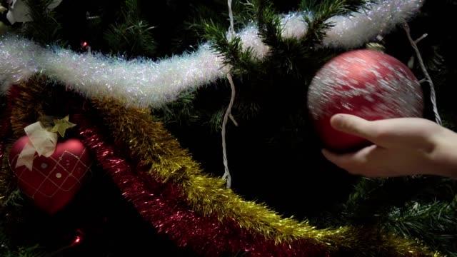 Hand man decorating on Christmas tree with Christmas glow lights video