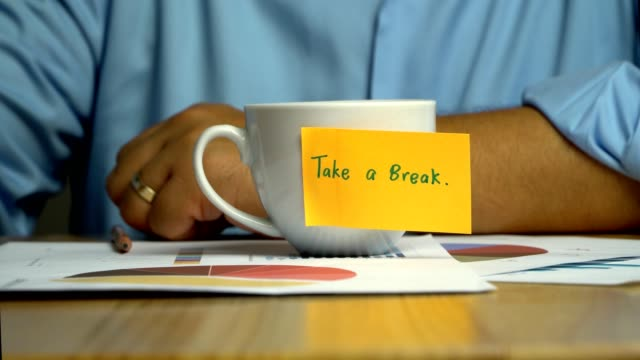 hand man holding a coffee cup and put it down on the annual report on coffee cup have a sticky note that says take a break. the concept of encouragement for colleagues - zachęta filmów i materiałów b-roll