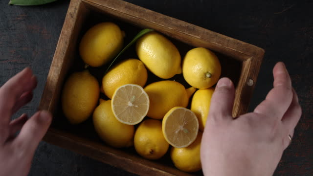 vídeos de stock e filmes b-roll de hand men put the box with lemons on table and take him. - inteiro