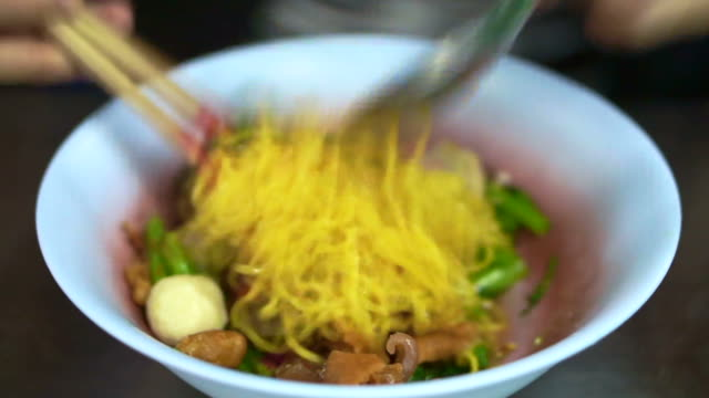 Hand mixing eating Yentafo, Thai red noodle with tofu and seafood video