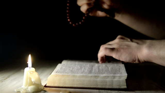 hand moves along a holy book