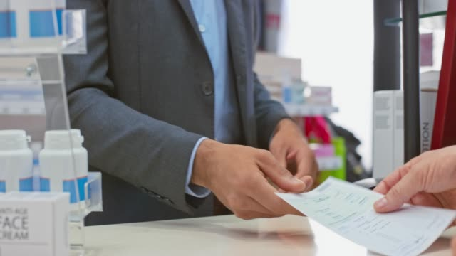 Hand of a business man giving his prescription to the pharmacists Medium handheld shot of the hands of a business man giving his medical prescription to the pharmacists standing behind the counter and waiting for his medicine. Shot in Slovenia. prescription stock videos & royalty-free footage