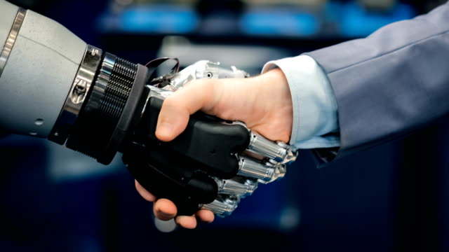 Hand of a businessman shaking hands with a Android robot. Hand of a businessman shaking hands with a Android robot. The concept of human interaction with artificial intelligence. cyborg stock videos & royalty-free footage