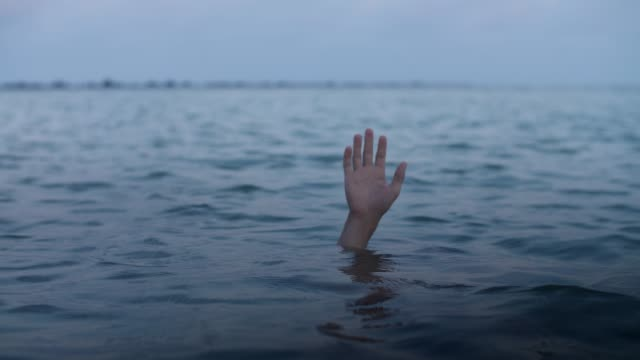 hand of a drowning man sinks into the water,concept of a person mired in debt and unable to help himself - długi filmów i materiałów b-roll