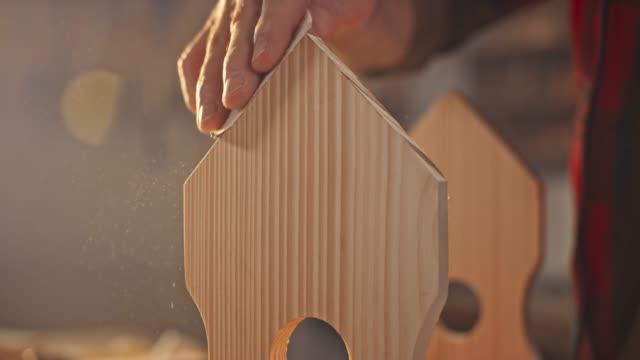 slo mo hand of a man finishing the surface of a bird house using sandpaper - carta vetrata video stock e b–roll