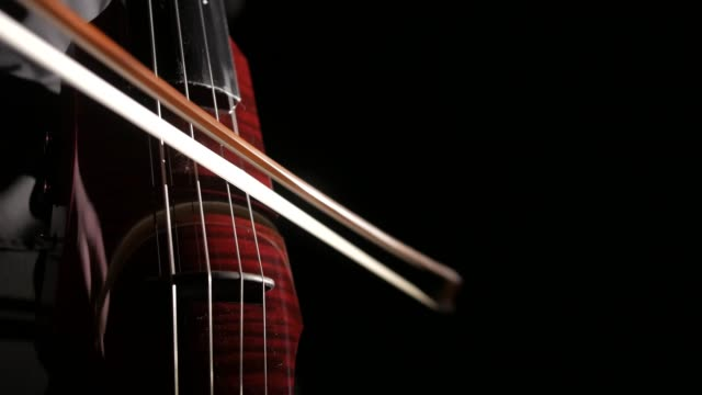 hand of a man playing an electric cello on a black background, closeup of strings, bow and fingerboard, isolated