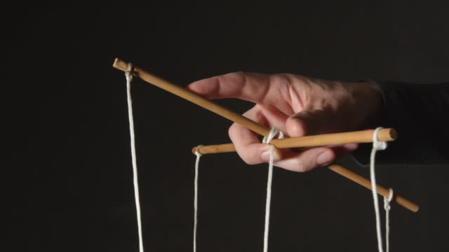 MANIPULATION: Hand of a puppeteer - Close up MANIPULATION: Hand of a puppeteer - Close up marionette stock videos & royalty-free footage