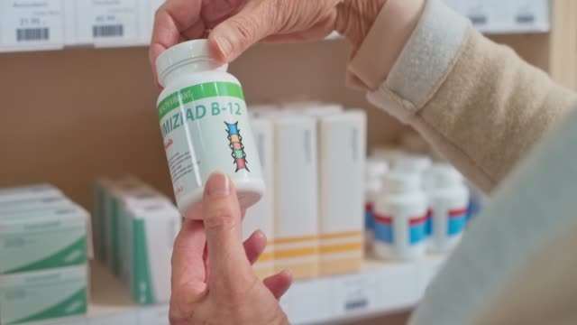 Hand of a senior Caucasian woman checking the label on the vitamin bottle at the drugstore