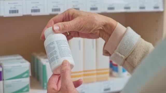 hand av en senior kvinna som tar en medicin flaska från hyllan på apoteket - pillerflaska bildbanksvideor och videomaterial från bakom kulisserna