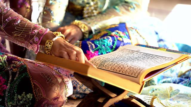 stockvideo's en b-roll-footage met hand van een jonge vrouw oost-type in de islamitische kleding en de prachtige hoofdtooi. houden en het lezen van de koran. - heilig geschrift