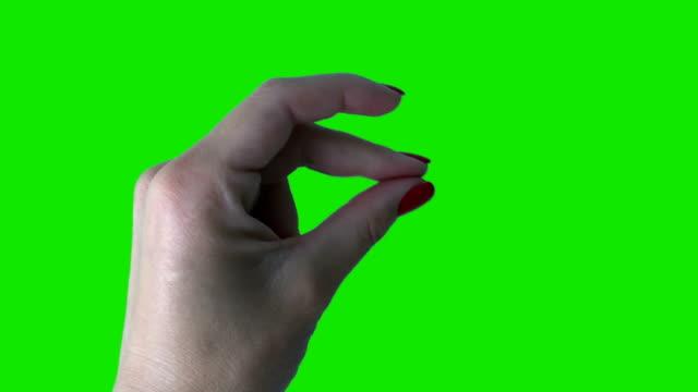 スナップを作るために美しい赤いマニキュアと若い女性の手。緑の背景 - 指点の映像素材/bロール