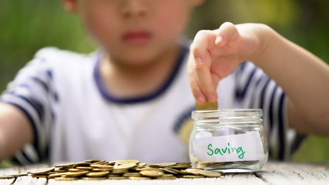 Hand of asian boy with golden coins saving golden ,saving concept, saving money ,business concept. video