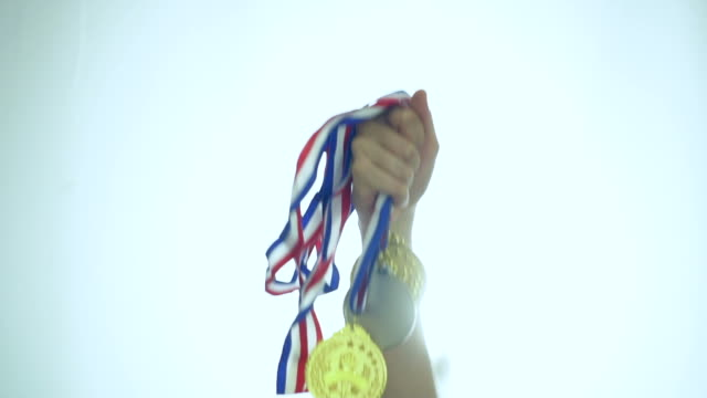 Hand of athlete celebrating the win with gold medals Hand of athlete celebrating the win with gold medals athleticism stock videos & royalty-free footage