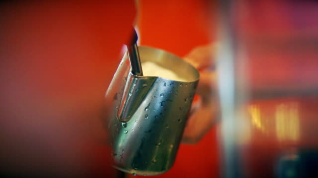 Hand of barista steaming milk in the stainless steel milk pitcher at the coffee shop.