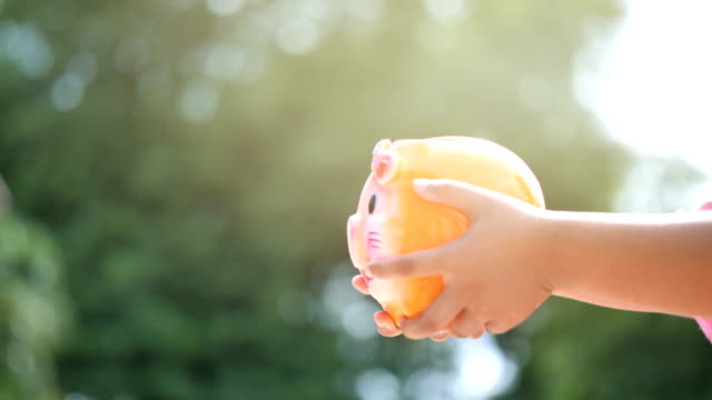 hand of boy holding piggy bank and putting coins, slow motion.  bokeh background. saving money and collecting money for the future. - risparmi video stock e b–roll
