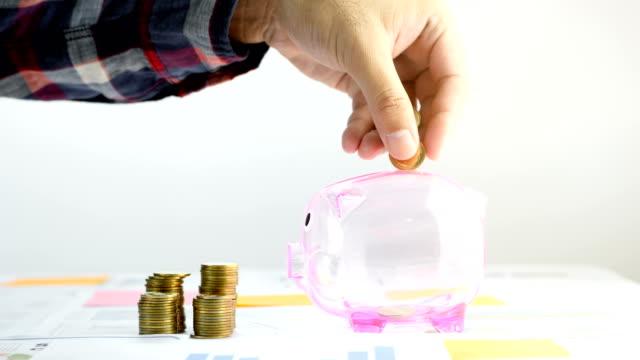 vidéos et rushes de main d'homme d'affaires, mettre la pièce de monnaie dans une tirelire. le concept de finance d'entreprise, comptabilité et économiser de l'argent. 4k vidéo slow motion - tirelire