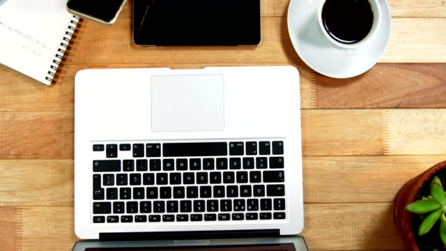 Hand of businesswoman using mobile phone at desk with coffee, laptop and digital tablet on table video