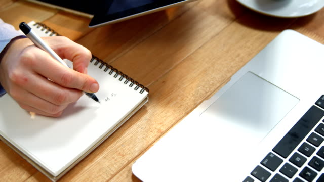 Hand of businesswoman writing on notebook at desk with digital tablet and laptop on table video
