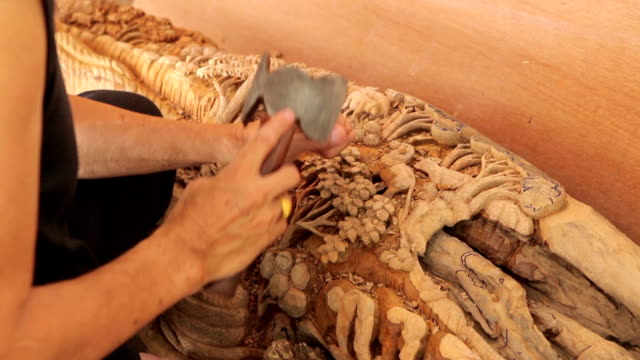 Hand of carver carving wood video