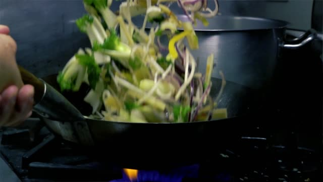hand of Chef Moving Vegetarian Salad In A Pan On Fire Slow motion tilt up medium shot of vegetables being flambayed and shaken into the air in a nice modern kitchen stir fried stock videos & royalty-free footage