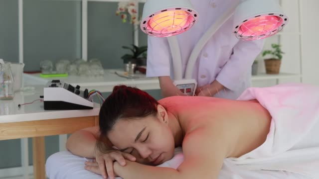 hand des arztes, der akupunkturtherapie durchführt. asiatische hündin unterzieht sich akupunkturbehandlung mit einer reihe von feinen nadeln in ihre gesichtshaut in klinik krankenhaus eingeführt - sauna und nassmassage stock-videos und b-roll-filmmaterial