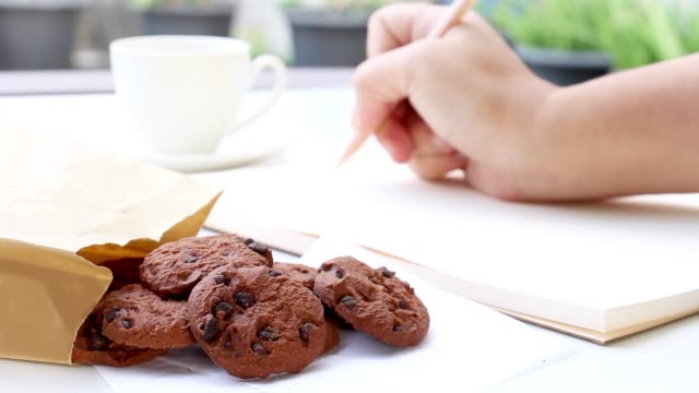 a hand of female with a wooden pencil writing in a notebook, placed on a white table with grab eat the a chocolate chip cookies in a paper bag and drink a coffee. - food delivery стоковые видео и кадры b-roll