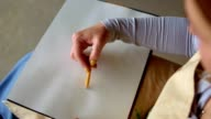 istock Hand of female with yellow manicure drawing at paper in her studio. Woman's hand draws. Designer clothes or tailor, animator, artist or illustrator. Female artist's hand sketching with a pencil on a light day. High angle view 1256423739