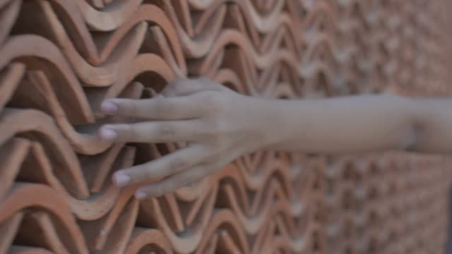 Hand of little girl touch gently on baked clay wall while walking.